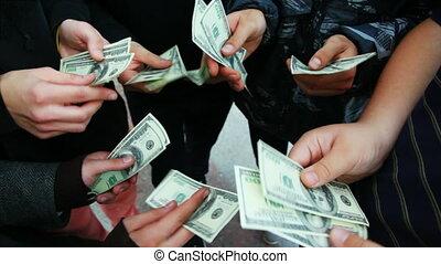 hands of five young men recount hundred dollar bills