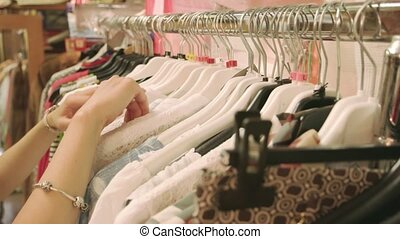 Hands of girl choosing clothes. Clothing on hangers. Sales...