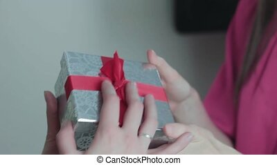 Hands of girl giving gift to friend near christmas tree close up