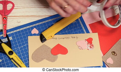 hands of girl making scrap Valentine greeting card