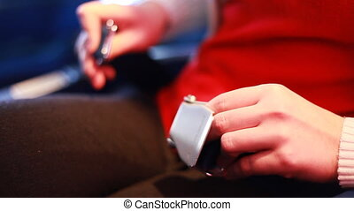 hands of girl sitting at passenger chair, button seatbelt before takeoff airplane