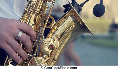 Hands of groom play on saxophone. Closeup hands of man playing golden alto saxophone with light effect. Men playing saxophone. Close up of men playing saxophone. golden alto in hands of young man.