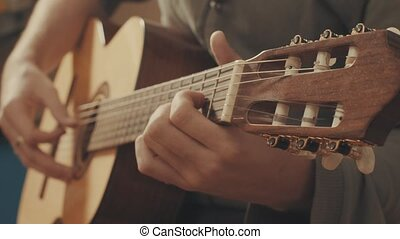 Hands of guitarist playing a guitar. Close-up
