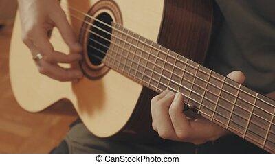 Hands of guitarist playing a guitar. Close-up 4K