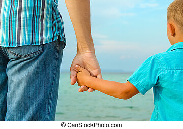 hands of happy parent and child at sea greece background