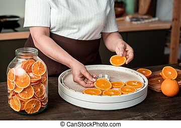 Hands of housewife putting orange slices on plastic trays of food dryer