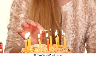 Hands of little boy in turn lights candles on the cake. slow...
