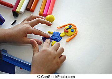 Hands of little girl making doll