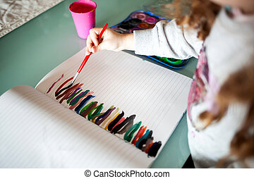 Hands of little girl painting with watercolors at home. Learn, education, happy childhood concept.