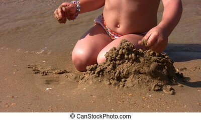 hands of little girl play with sand on beach