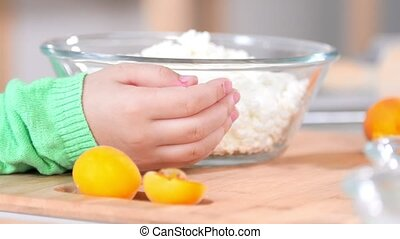 Hands of little girl with glass bowl of cottage cheese on...