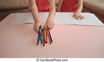 Hands of little girls with colored pencils close-up. Drawing at the table.