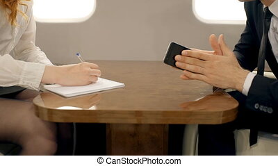 Hands of male boss and female secretary working together in business jet.