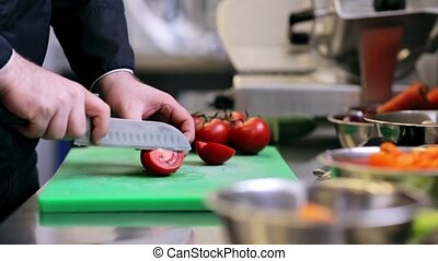 hands of male chef chopping tomatoes in kitchen