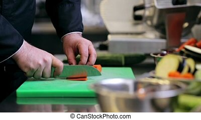 hands of male chef cook chopping carrot in kitchen -...