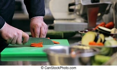 hands of male chef cook chopping carrot in kitchen