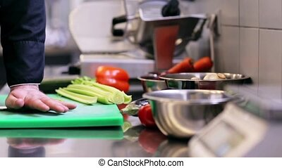 hands of male chef cook chopping celery in kitchen -...