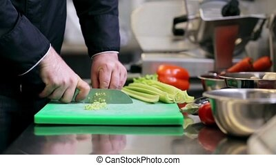 hands of male chef cook chopping celery in kitchen