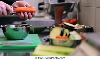 hands of male chef cook peeling carrot in kitchen - cooking,...