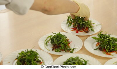 Hands of male chef serving salad on plate - Hands of male...