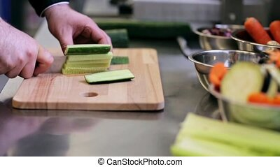 hands of male cook chopping cucumber in kitchen