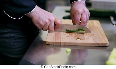 hands of male cook chopping cucumber in kitchen - cooking,...