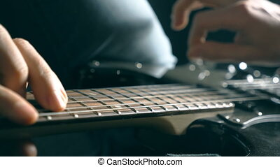 Hands of male musician playing at electric guitar. Mens arms...
