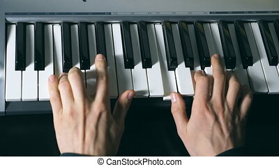 Hands of male musician playing at synthesizer. Mens arms...