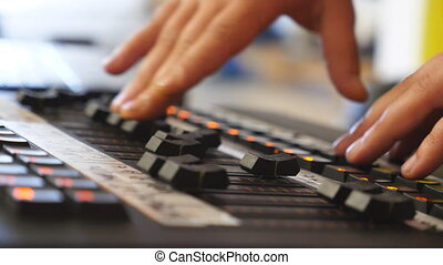 Hands of male sound engineer presses the keys and moves...