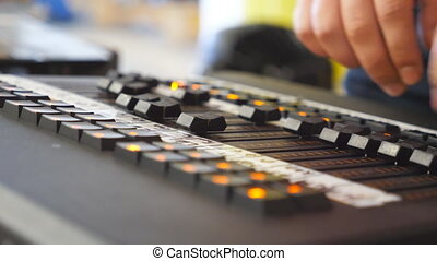 Hands of male sound engineer presses the keys and moves buttons of soundboard . Arms of man working on professional digital audio channel mixer. Amplifier and balance of sound. Close up Slow motion