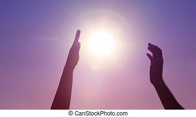 hands of man and woman contacting against sun on sky