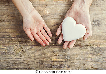 Hands of man and woman holding a heart together.