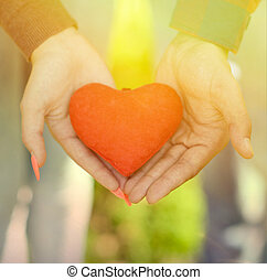 Hands of man and woman holding red heart