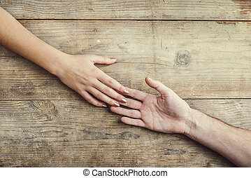 Hands of man and woman holding together.
