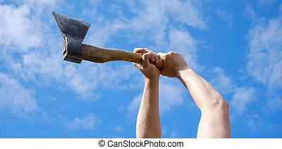 Hands of man choping firewood with axe on blue sky