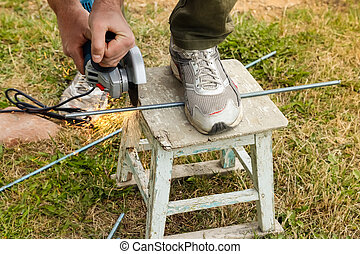 Hands of man holding electric angle grinder and cutting metal, sparks from tool.