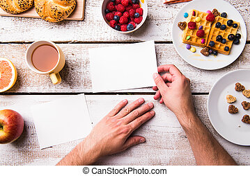 Hands of man holding empty greeting card. Breakfast meal.