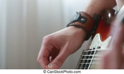 Hands of man playing electric guitar.