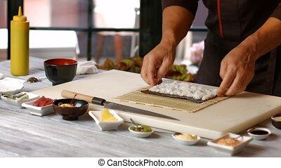Hands of man preparing sushi.