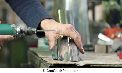 Hands of man using drill. Drilling holes in metal part. Best...