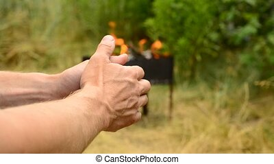 Hands of man with fire in brazier on background