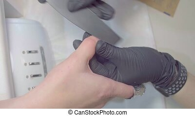 Close up hands of manicurist polishing client's nails