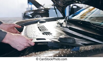 Hands of mechanic in automobile garage checking hood for the luxury car