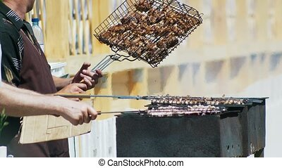 Hands of men grilling kebab on barbecue outdoors, close up