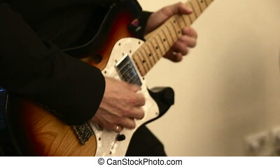 hands of men play on electric guitar