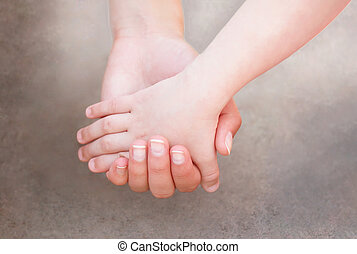 Hands of mother and child together