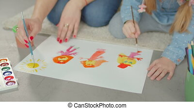 Hands of mother and daughter painting on floor - Close-up of...