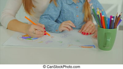 Hands of mother and kid creating artwork at desk - Closeup...