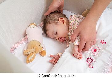 Hands of mother caressing her baby girl sleeping