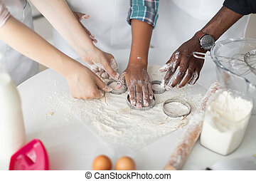 Hands of multiracial family with child squeezing out the dough using cookie cutters